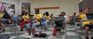 Students face the classroom in their fun yellow t-shirts!