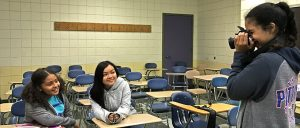 Students practice taking portraits of each other in classroom.