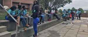 TAG students sit along the cement steps.