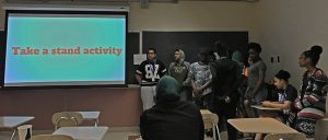 """Students stand in a clump on the left side of """"Take a Stand"""" activity slide by the Strong Disagree side."""