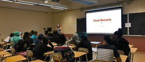 """""""Food desert"""" displays on screen as students sit in the back and watch their instructor define and explain what words mean."""