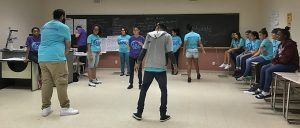 Students stand and sit in circle as two students practice their steps for bachata.