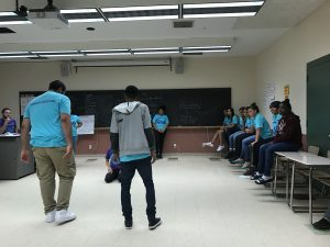 Two male students are in the middle of the dance floor while everybody else watches.