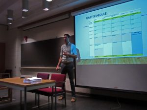 Jeff giving students an overview of what the schedule of their summer will consist of standing in front of the slide.