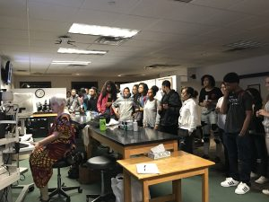 A pool of students are watching Dr. Maureen sit on the stool explain the operation of the slit lamp