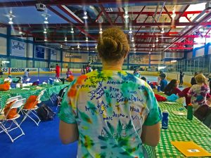 Back of councilor's colorful tie-dye t-shirt standing in front of the gym.