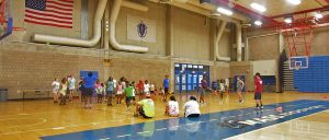 Handful of students mentors sit, jump rope and talk on the floor while a pool of students stand and dance in the gym to celebrate their last day of camp.