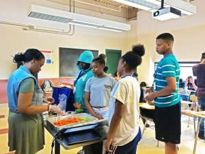 Students line up along the right side of the direction the camera is facing, on the opposite side of Daphney who is distributing the carrots and celery with a cup of hummus.