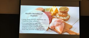 """Photograph of different types of sources of protein (turkey, ham, eggs, nuts and salmon, cheese and milk) behind text that says: """"Health Benefits of Protein: 1. Some food sources of protein are healthier than others. 2. It is important to take into consideration the type and amount of fat in the food, the sodium (salt), and any nutrients that may provide health benefits."""""""