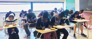 Students face their papers on desk while they hold their pencil in other hand deep in focus.