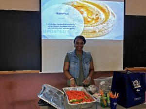 Behind is a photo of hummus. Infront of the screen, Daphney stands in front of aluminum container of carrots and celery with hummus and apple sauce on the side. Health and nutrition teacher stands in front of chalkboard ready to serve.
