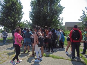 A clump of students stand together with their backpacks in front of garden.