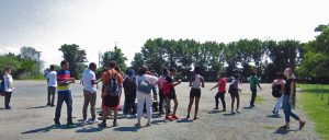 Students stand in rocky empty parking lot by the church with the garden. Students in the middle are in front of the cooler and the box of snacks, while the students on the side leave with snacks or enter waiting for snacks.