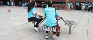 Two students sit at table outside by McCormack Hall for lunch.
