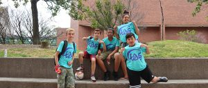 Group of five students show off their blue TAG t-shirts!
