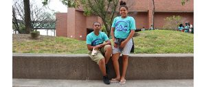 Two students (male and female) pose in front of stairs with their blue TAG t-shirts!