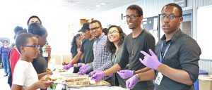 Team members all smile into the camera as they are in the middle of serving students lunch.