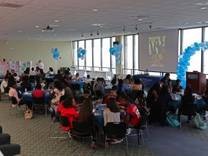 Blue and white balloons are flying by the windows and projector. Students sit at circle tables.