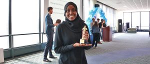 Student with hijab poses with trophy in her hand as she makes way to her seat.