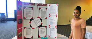 """Student stands on the right of her """"Boston College Poster"""" smiling."""