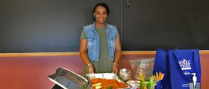 Daphney stands in front of aluminum container of carrots and celery with hummus and apple sauce on the side. Health and nutrition teacher stands in front of chalkboard ready to serve.