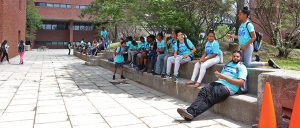 Students in blue TAG t-shirts sit on cement with their lunches.