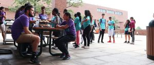 Students line up for lunch by picnic table where mentors in purple t-shirts sit.