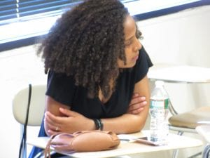 A focused girl sitting in the classroom brainstorming Ideas.