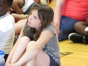 A girl facing forward on the floor.