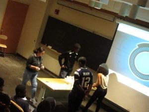 Students standing two opposite sides of the table with cups on the table.