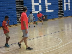 The student are in the gym playing basketball