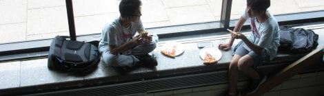 Two friendly students  talking while eating their lunch.