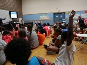A lot of children have their hands raised to answer a quetion.