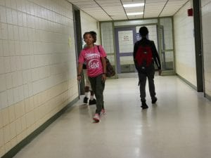 two boy students, and a TA walking down the hallway.