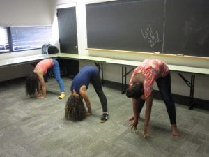 three girls bending down for exercise.