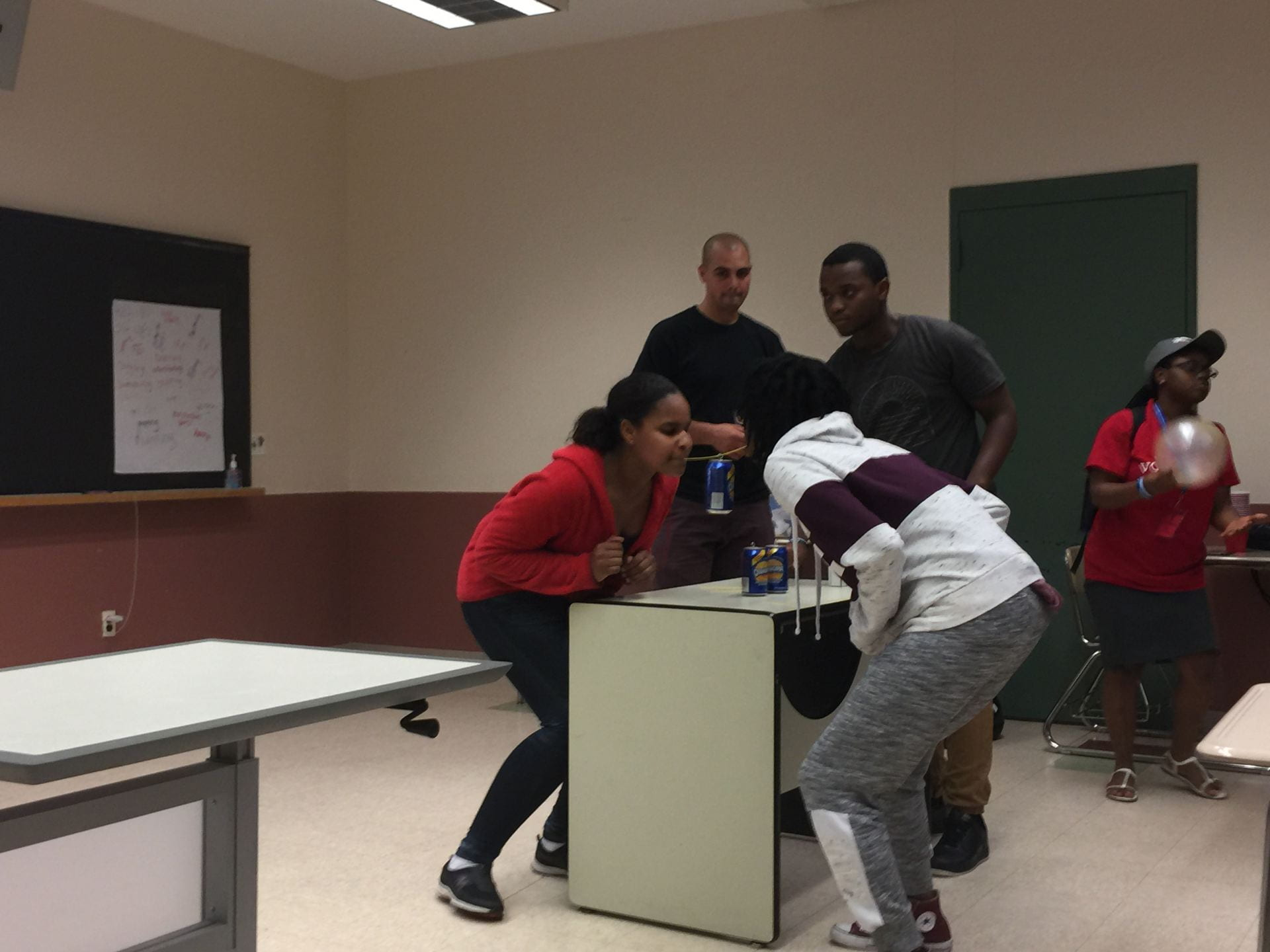 students try to build a tower from Pepsi bottles, balancing them on a single spaghetti