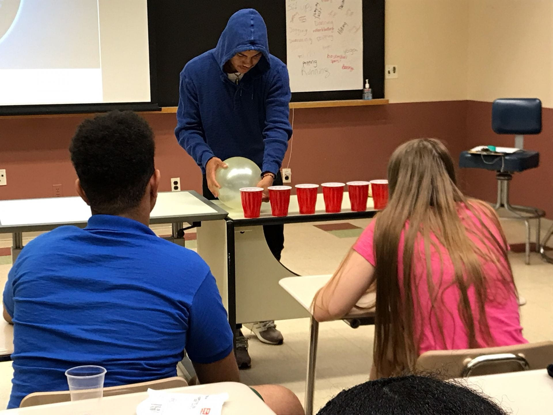 a student tries to blow away plastic cups