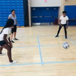 students pass the ball to each other in a game of four square