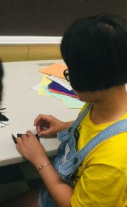 a student works diligently to perfect her orogami piece