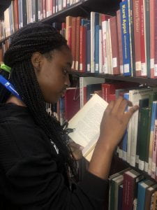Student reading book by library shelves.