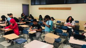 image of students taking a picture of another students art work.