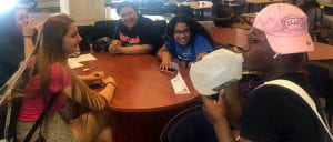 Group of students and a TA laughing and smiling at a round table.