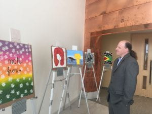 The urban scholars director walks around and looks at a painting from the students in the art class