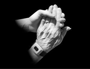 caregiver holds elderly hands