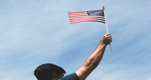 woman of color waving American flag