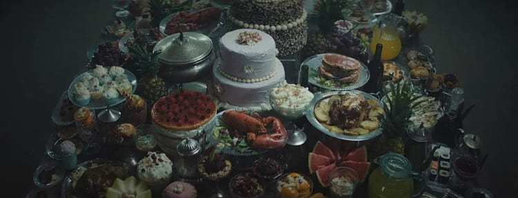 a table laid with a feast of beuatifully prepared gourmet food. Cake and fruit are prominent.