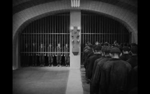 Workers of Metropolis at shift change. Waiting to be allowed in/out through a jail-like barred entrance.