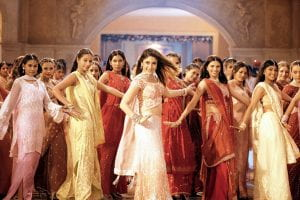 a group pf Indian women in beautiful saris perform a Bollywood style dance number