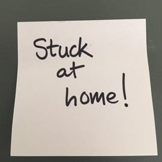 """Post-it note with """"Stuck at Home!"""" written on it."""