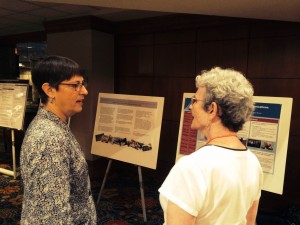 Joanne Riley, University Archivist and Curator of Special Collections in the Healey Library at UMass Boston (left) and an SAA conference attendee discuss the department's poster.